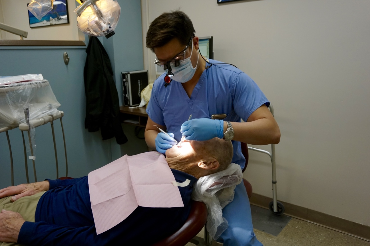 Jeffrey Pan, student commencement speaker for the UConn School of Dental Medicine Class of 2016, with a patient in the dental clinic. (Photo by Ze Horak)